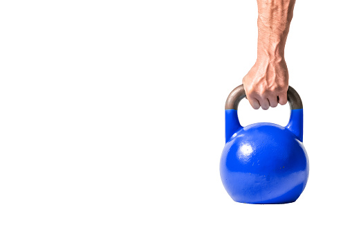 Strong Muscular Man Hand With Muscles Holding Dark Blue Heavy Kettlebell Partially Isolated On White Background Stock Photo - Download Image Now