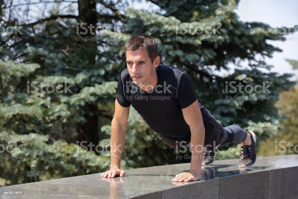 Strong muscular man push ups plank workout onsummer day. Sport, fitness, active lifestyle concept stock photo
