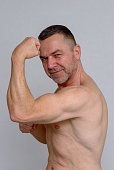 istock Strong muscular man showing off his biceps 932846620