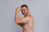 istock Strong muscular man showing off his biceps 932848572