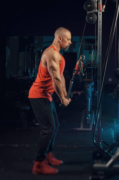 starker muskulöser mann trainiert im fitnessstudio - killer workouts stock-fotos und bilder