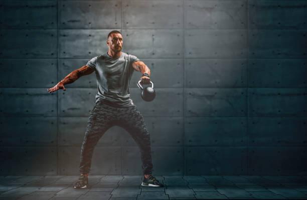 hombres musculosos fuertes, ejercicio de atleta de entrenamiento cruzado con kettlebell. copiar espacio - pesa rusa fotografías e imágenes de stock