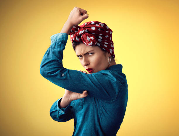 Strong, on the inside and the outside Studio portrait of an attractive young woman flexing her bicep while standing against a yellow background women's rights stock pictures, royalty-free photos & images