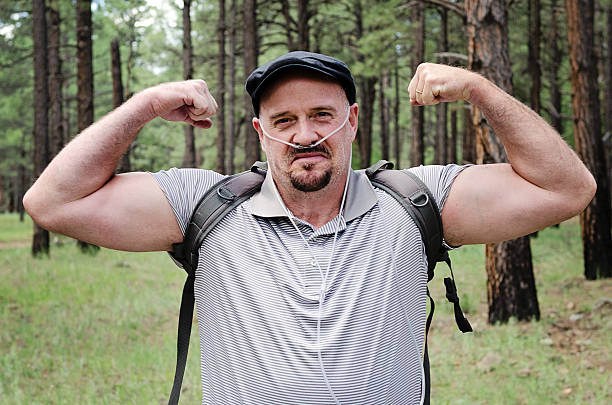 Strong Patient Middle aged man flexes his muscles as he hikes in the woods wearing therapeutic oxygen. oxygen tube stock pictures, royalty-free photos & images