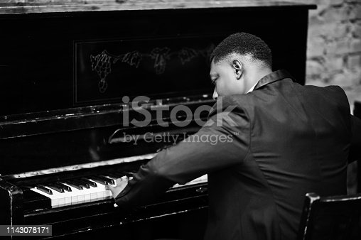 Back of strong powerful african american man in black suit play piano.