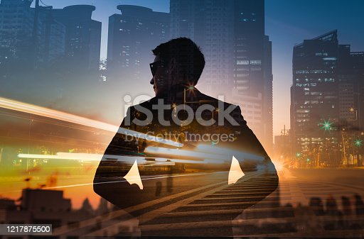 1079450712 istock photo Strong, powerful, successful and determined business man standing in futuristic modern city setting. Double exposure 1217875500