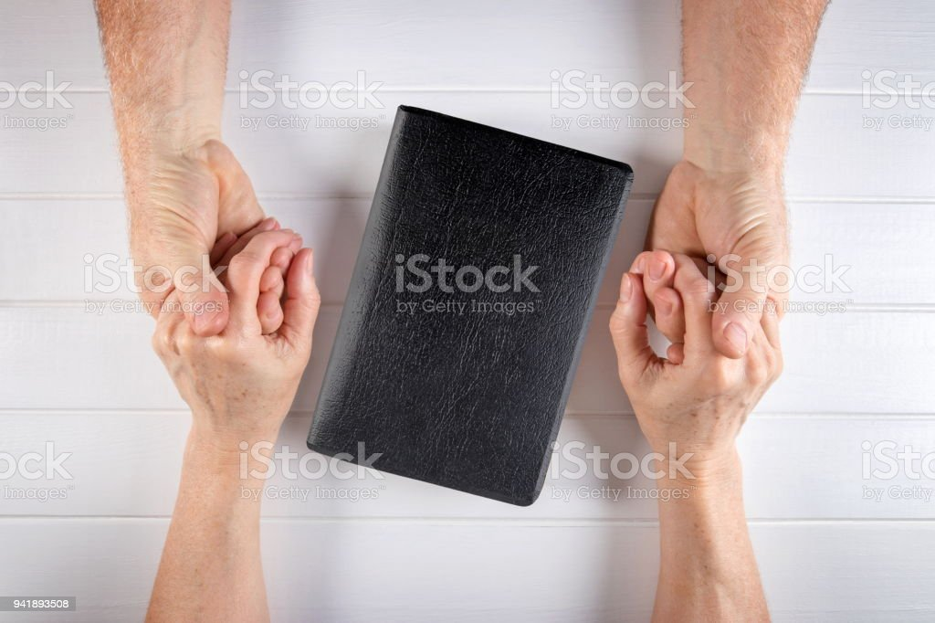 Strong relationship of a family to old age around the Bible stock photo