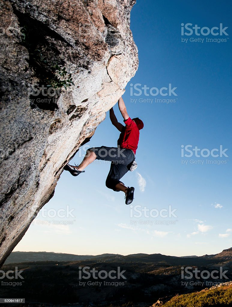 Strong rock climber on a steep cliff stock photo