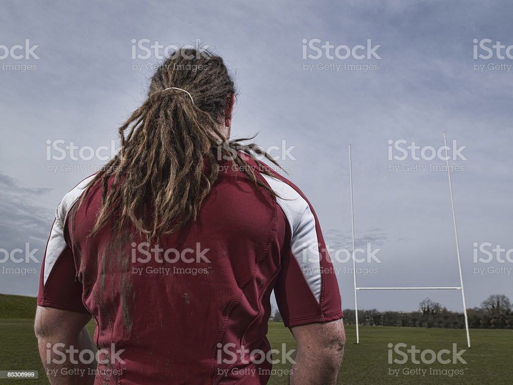 Strong rugby player on pitch facing rugby posts royalty-free stock photo