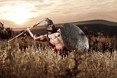 Strong Spartan warrior in battle dress with a shield and a spear