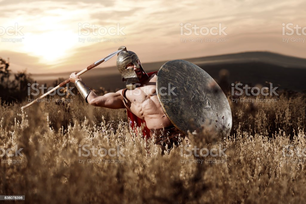 Strong Spartan warrior in battle dress with a shield and a spear stock photo