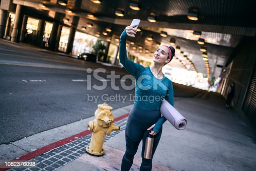 1091470492 istock photo Strong sports woman taking a selfie with a mobile phone on the street sidewalk 1082376098