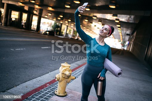 1091470492 istock photo Strong sports woman taking a selfie with a mobile phone on the street sidewalk 1093219500