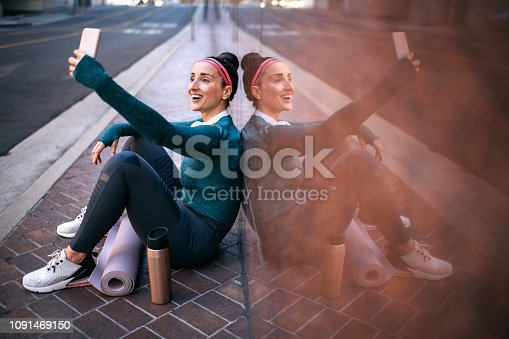 1091470492 istock photo Strong sports woman taking a selfie with a mobile phone while sitting with her back against a marble building wall in a city street 1091469150
