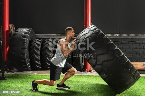 Tire flip exercise. Strong sportsman during his cross training workout.