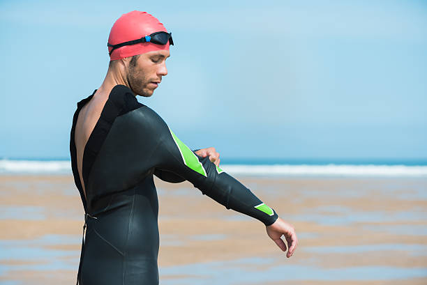 Strong triathlon sportsman adjusting wet suit  for open water workout Portrait of a strong triathlon sportsman adjusting wet suit motivated for his open water summing workout routine on a beach training for a triathlon competition outdoor at sea. wetsuit stock pictures, royalty-free photos & images