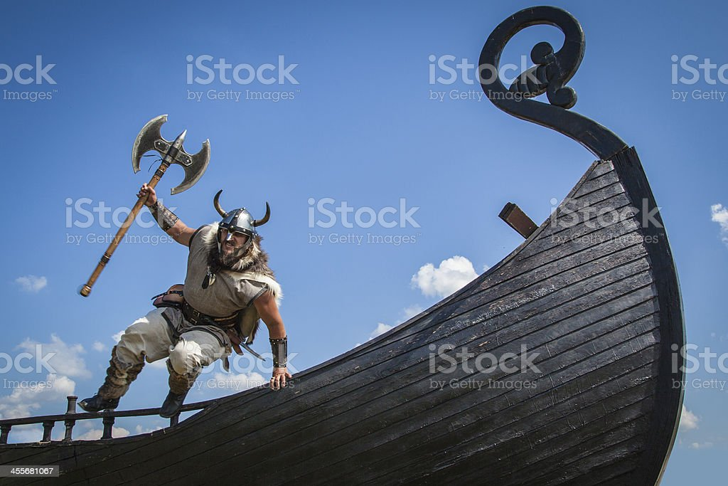 Strong Viking jumping from his ship to attack stock photo