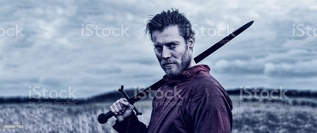 Strong warrior stands on the battlefield with a sword stock photo