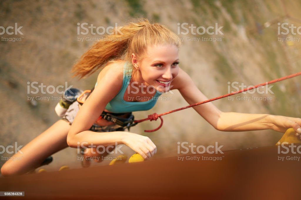 Strong woman and business success concept. Top view of young caucasian pretty woman practicing climbing on artificial rock wall outdoors. Slim sporty blonde training speed bouldering session stock photo