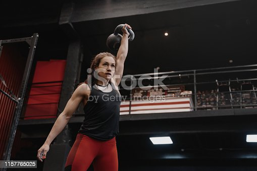 Strong woman exercising with a kettlebell at the gym. Female doing functional training, lifting weights. Copy space
