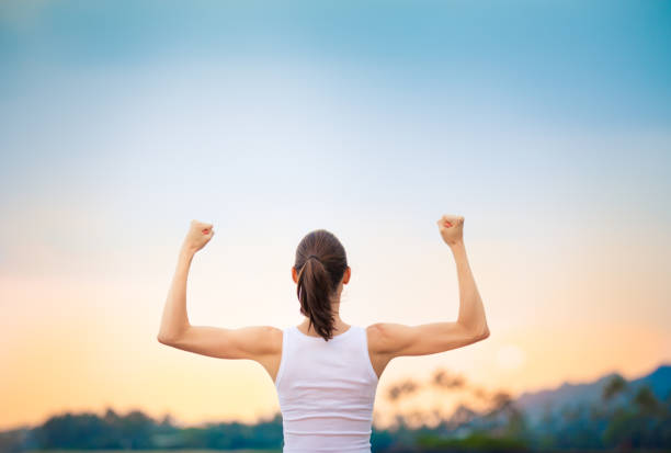 Strong woman flexing her muscles against sunset. stock photo