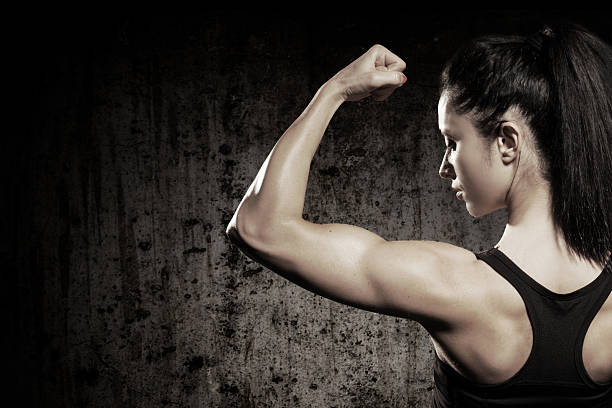 A strong woman flexing her muscles stock photo