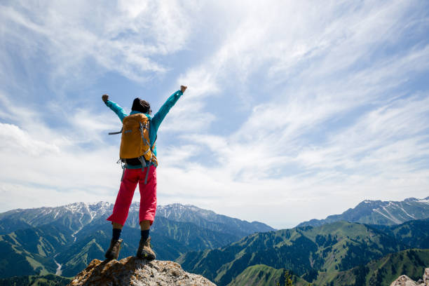 Strong woman hiker outstretched arms stand at cliff edge on mountain top stock photo
