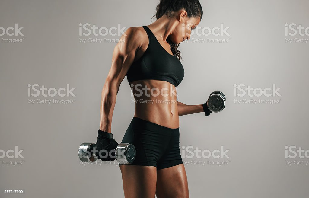 Strong woman lifting weights over gray background – Foto
