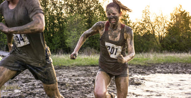 Strong Woman Young adult athletes are testing their endurance during an extreme challenge of mud running outdoors. mud run stock pictures, royalty-free photos & images