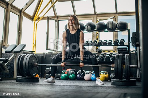 istock Strong woman weightlifting 1248890502