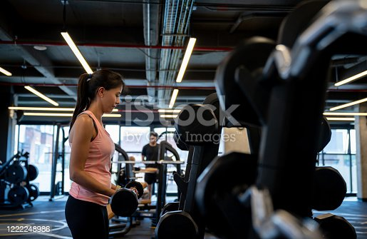 Portrait of a strong woman working out at the gym using free-weights – active lifestyle concepts