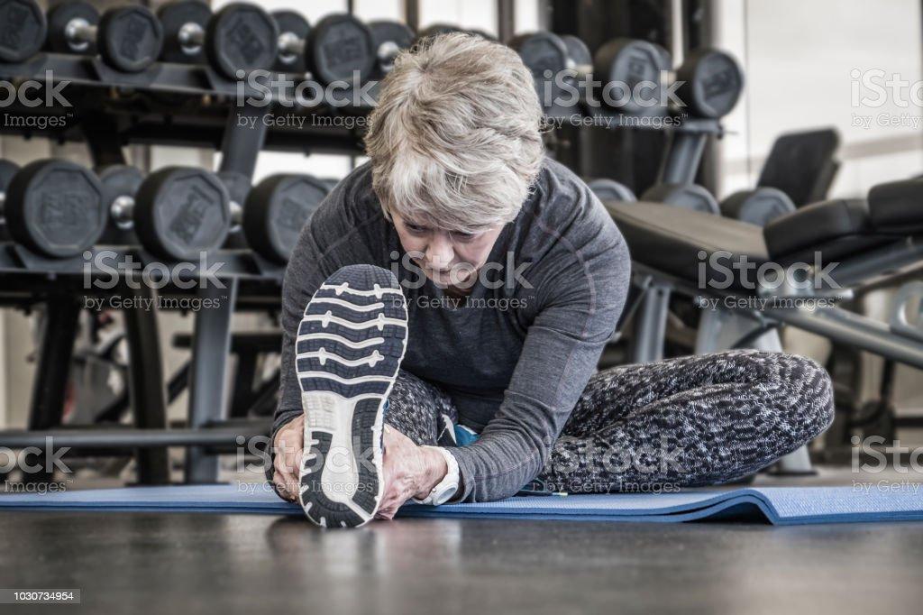 senior woman gym workout floor exercises - stretching