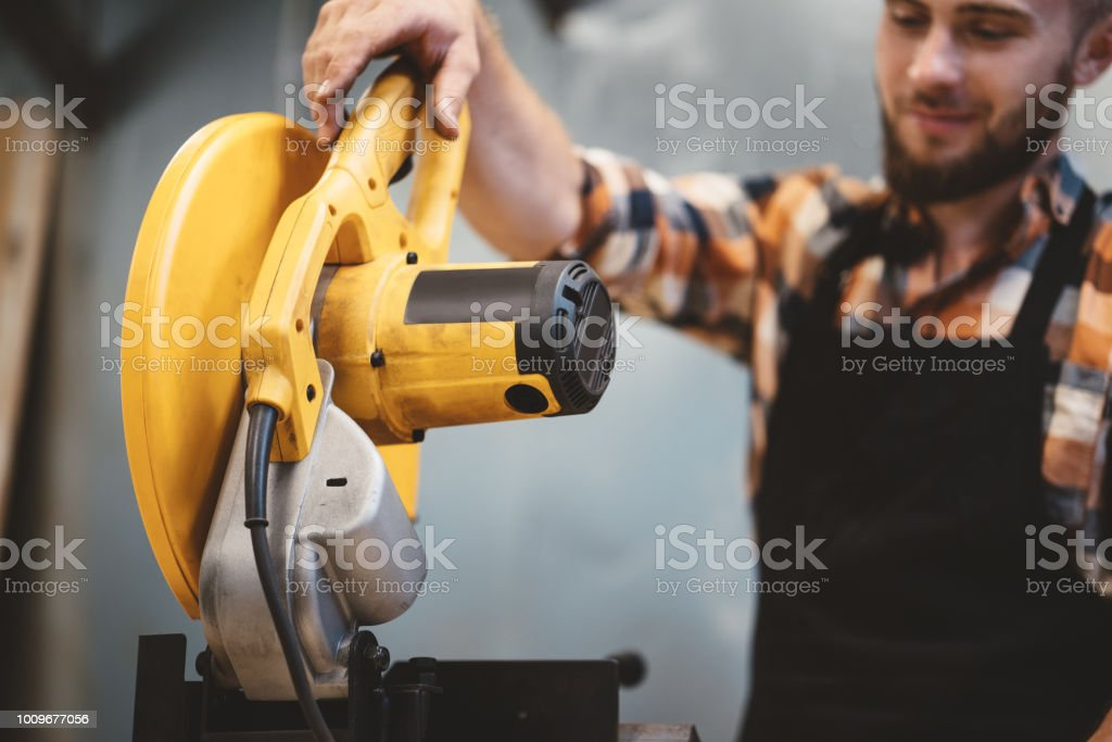 Strong worker using angular grinding machine in workshop. Servicing of machines. Workflow at the factory stock photo