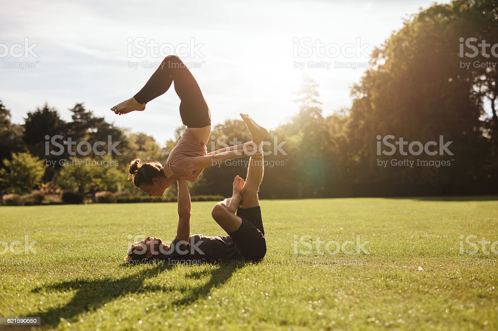 Strong young couple doing acroyoga workout Strong young couple doing acroyoga workout. Man and woman in park practising pair yoga in morning. Acrobatic Activity Stock Photo