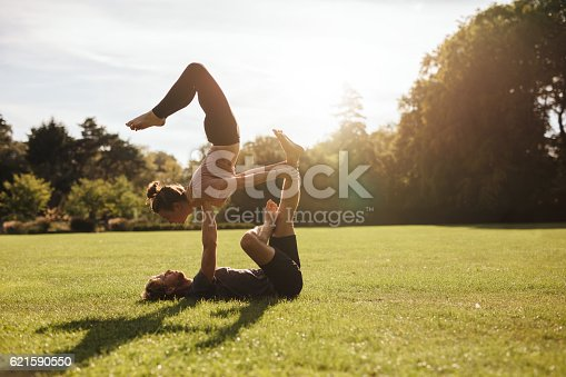 istock Strong young couple doing acroyoga workout 621590550