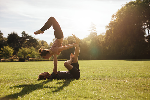 Strong Young Couple Doing Acroyoga Workout Stock Photo - Download Image Now