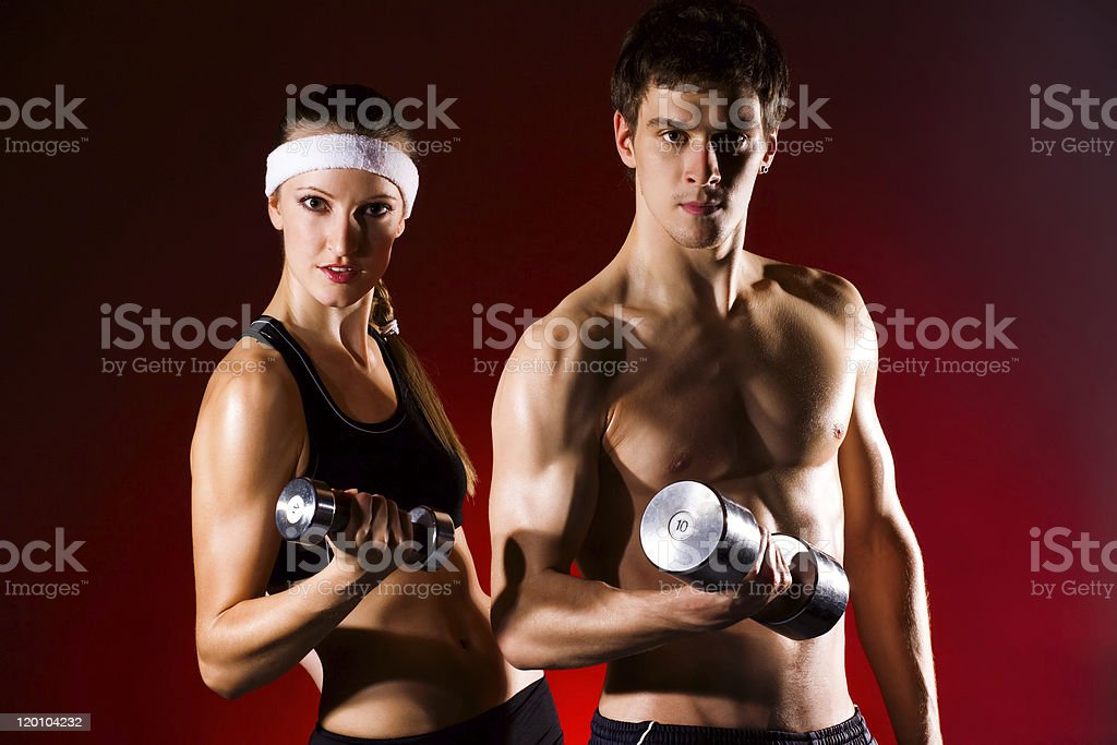 strong young couple working out with dumbbells royalty-free stock photo