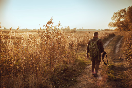 Strong young hunter with red beard holding his gun and walking along the dirt road under blue sky