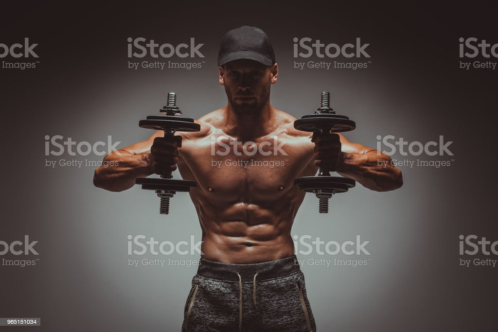 Strong young man bodybuilder performing exercise for biceps with heavy weights in both hands. Concept Gym Life Style.Toned Image. royalty-free stock photo