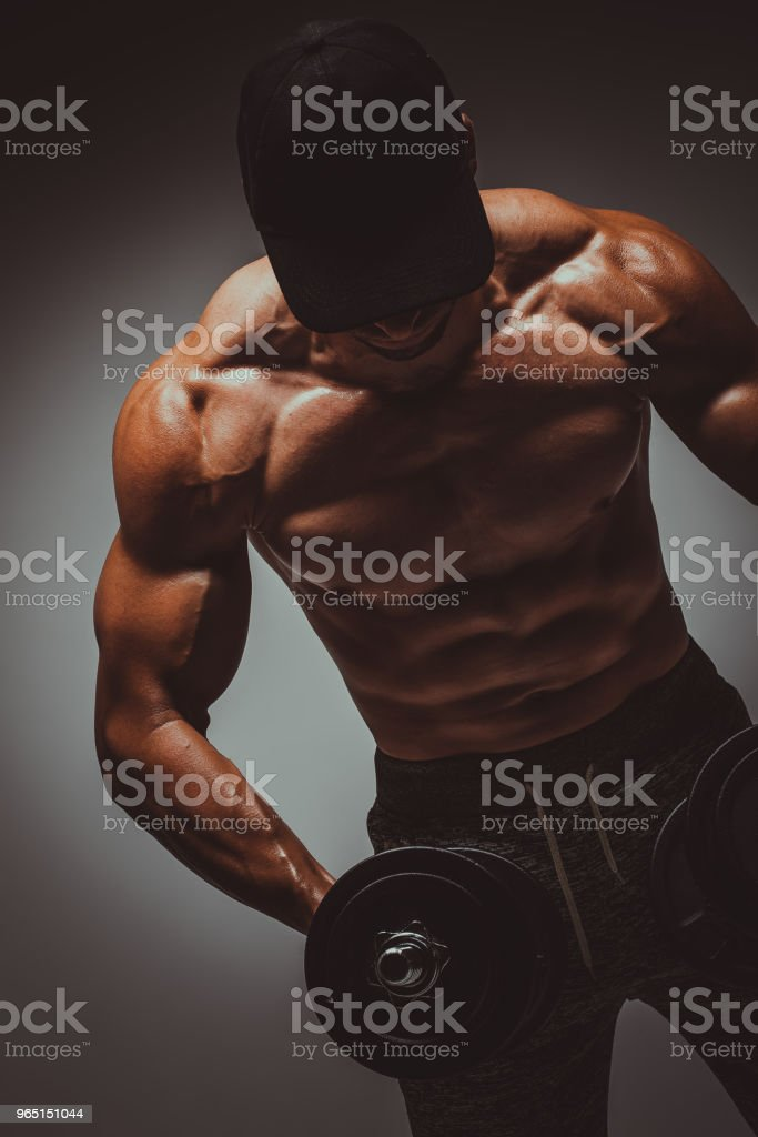 Strong young man bodybuilder performing exercise for biceps with heavy weights in both hands. Concept Gym Life Style.Toned Image. zbiór zdjęć royalty-free