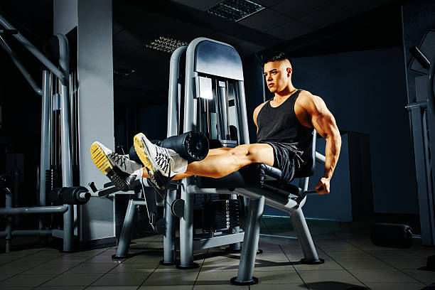 Strong young man doing legs exercise in the gym Strong young man doing legs exercise in the gym exercise machine stock pictures, royalty-free photos & images
