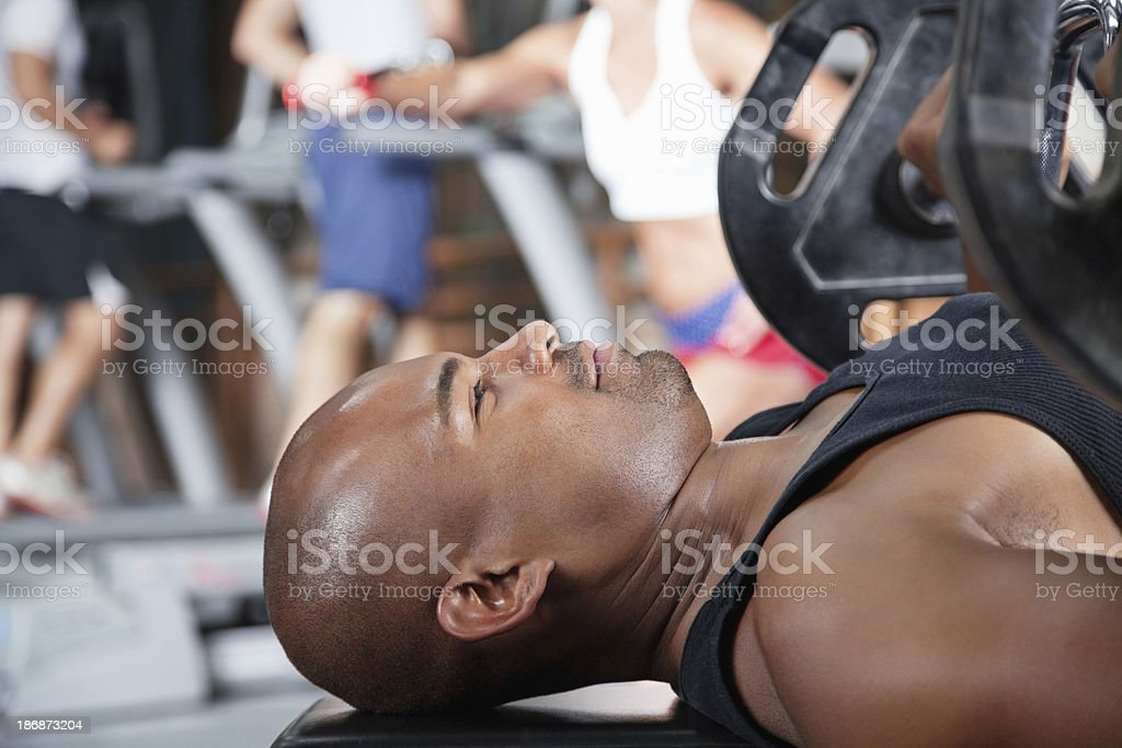 Strong young man lifting benchpress in the gym royalty-free stock photo