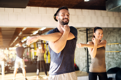 istock Strong young smiling athletes stretching in a gym . 1034925554