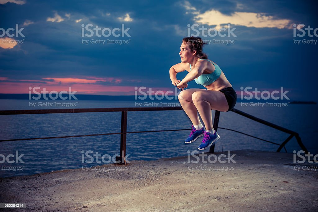 Strong young woman doing plyometric exercises on pier stock photo