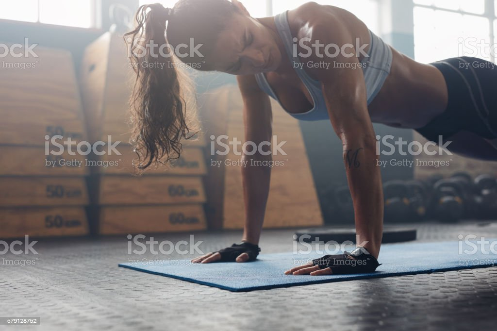 Strong young woman doing push-ups in gym stock photo