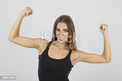 657442382istockphoto Strong young woman flexing muscles 889679560