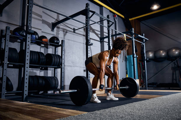 Strong young woman performing the deadlift exercise stock photo