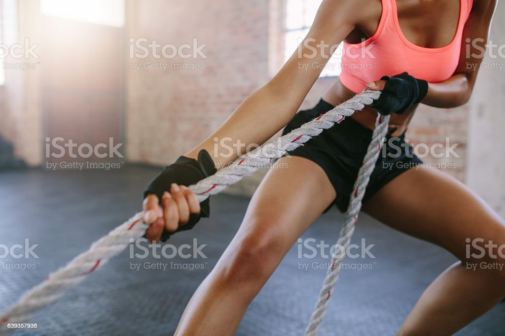 Strong young woman pulling rope at a gym stock photo