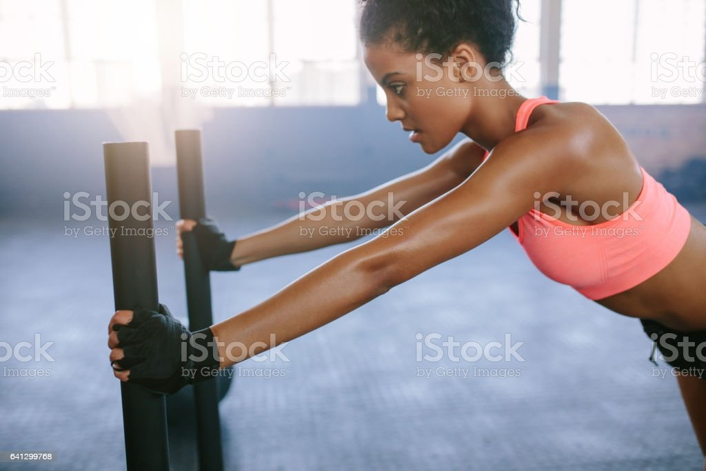 Strong young woman pushing the sled at gym stock photo