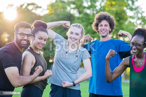 A multi ethnic group of young adults are in a fitness group in a park. Here they smile and make funny faces while they hold poses and flex their muscles together.